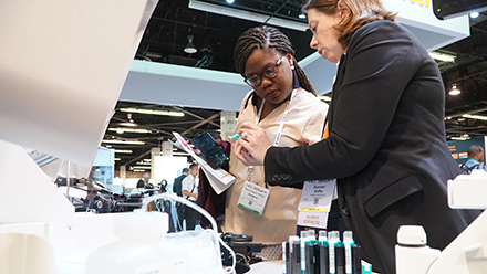 An African American laboratory medicine professional and a white female exhibitor look at a diagnostic instrument together at the AACC Clinical Lab Expo.